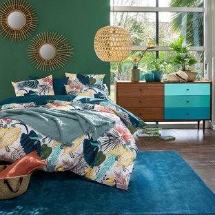 На фото: спальня в современном стиле с зелеными стенами и коричневым полом без камина с