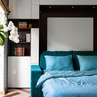 Imagen de dormitorio principal y ladrillo, bohemio, pequeño, ladrillo, con paredes blancas, suelo de madera en tonos medios, suelo multicolor y ladrillo