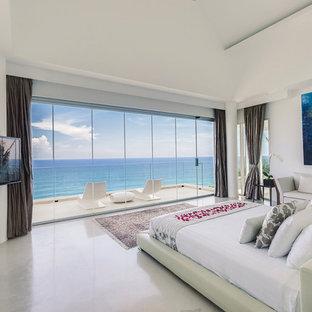 На фото: спальня в современном стиле с белыми стенами, бетонным полом и серым полом