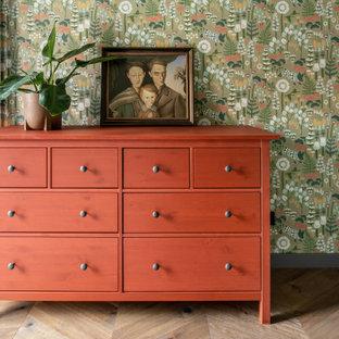 Cette photo montre une grand chambre d'amis tendance avec un mur vert, un sol en bois brun, un sol marron et du papier peint.