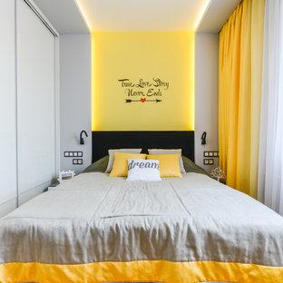 Foto de dormitorio principal, actual, de tamaño medio, con paredes grises y suelo de madera en tonos medios