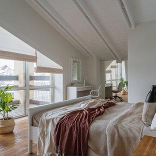 Immagine di una grande camera matrimoniale scandinava con pareti bianche, pavimento in legno massello medio e travi a vista