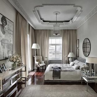 Réalisation d'une chambre parentale design avec un sol en bois foncé, un sol marron et un mur gris.