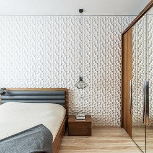 Foto di una camera matrimoniale contemporanea con pareti bianche, parquet chiaro e pavimento beige