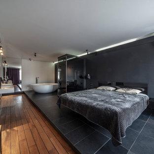 На фото: большая хозяйская спальня в современном стиле с черными стенами, темным паркетным полом и коричневым полом с