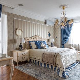 На фото: хозяйская спальня в классическом стиле с темным паркетным полом, коричневым полом и бежевыми стенами с