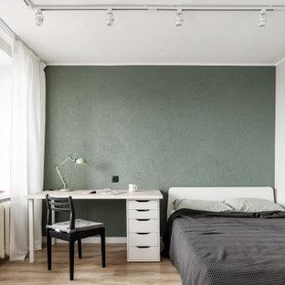 Свежая идея для дизайна: маленькая спальня в современном стиле с зелеными стенами, полом из ламината и коричневым полом - отличное фото интерьера