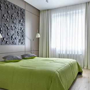 Immagine di una camera matrimoniale design con pareti beige, nessun camino e parquet chiaro