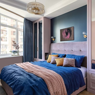 Small transitional master bedroom in Moscow with blue walls, medium hardwood floors and brown floor.