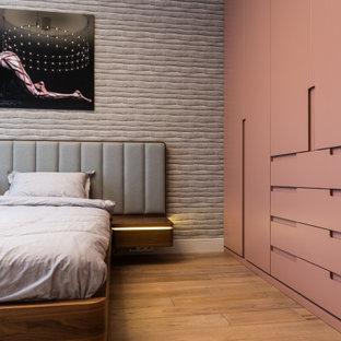 Idéer för att renovera ett funkis huvudsovrum, med grå väggar, mellanmörkt trägolv och brunt golv