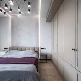 На фото: хозяйская спальня в современном стиле с серыми стенами, светлым паркетным полом и бежевым полом с
