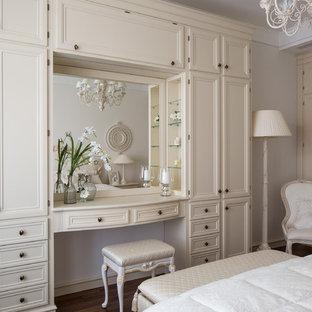 Modelo de dormitorio tradicional con paredes blancas y suelo de madera oscura