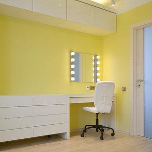 Inredning av ett modernt litet huvudsovrum, med gula väggar, laminatgolv och beiget golv