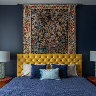 Exemple d'une chambre parentale tendance avec un mur bleu.