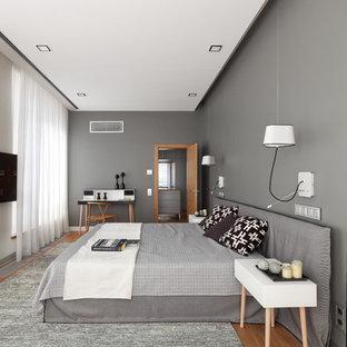 Bild på ett stort funkis huvudsovrum, med grå väggar, mellanmörkt trägolv och brunt golv
