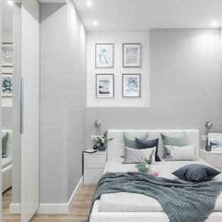 Стильный дизайн: маленькая хозяйская спальня в современном стиле с серыми стенами, полом из ламината и коричневым полом - последний тренд