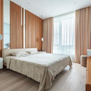 Diseño de dormitorio principal, actual, de tamaño medio, sin chimenea, con paredes marrones, suelo laminado y suelo beige