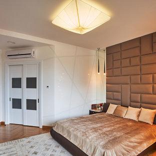 Imagen de dormitorio principal, actual, de tamaño medio, con paredes marrones, suelo de madera clara y suelo amarillo