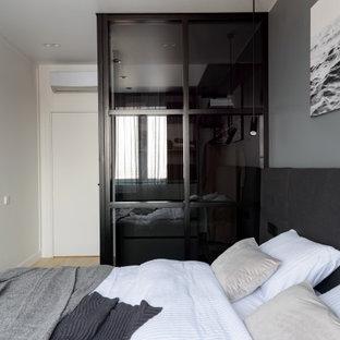Foto de dormitorio principal, actual, de tamaño medio, con paredes grises y suelo laminado