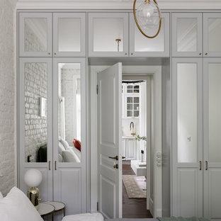 Ejemplo de dormitorio principal y ladrillo, nórdico, de tamaño medio, ladrillo, con paredes blancas, suelo vinílico, suelo marrón y ladrillo