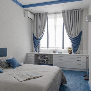 Inredning av ett modernt sovrum, med vita väggar, heltäckningsmatta och blått golv