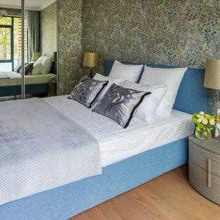 Modelo de dormitorio contemporáneo con paredes verdes y suelo de madera en tonos medios