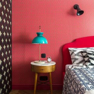 Exemple d'une chambre parentale éclectique avec un sol en bois brun, un mur rouge et un sol marron.