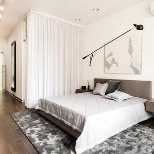 Стильный дизайн: хозяйская спальня в современном стиле с белыми стенами, темным паркетным полом и коричневым полом - последний тренд