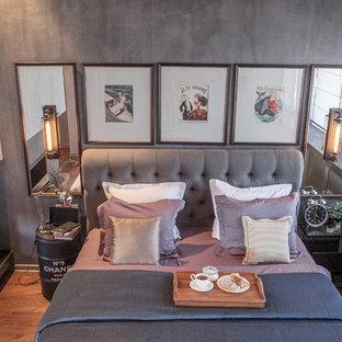 Ejemplo de dormitorio principal, industrial, con paredes grises, suelo de madera en tonos medios, marco de chimenea de hormigón, suelo marrón y chimenea de doble cara