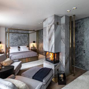 Неиссякаемый источник вдохновения для домашнего уюта: хозяйская спальня в современном стиле с серыми стенами, камином, фасадом камина из камня и паркетным полом среднего тона