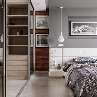 Mittelgroßes Modernes Hauptschlafzimmer mit grauer Wandfarbe, beigem Boden, Holzwänden und hellem Holzboden in Sonstige