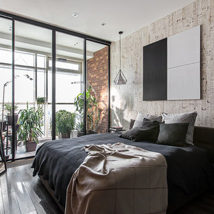 This is an example of an industrial master bedroom in Moscow with dark hardwood floors and grey walls.