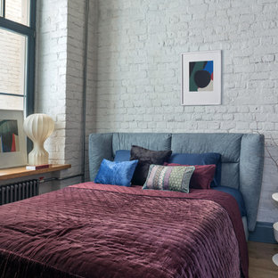 Идея дизайна: хозяйская спальня в стиле лофт с белыми стенами, паркетным полом среднего тона, коричневым полом и кирпичными стенами