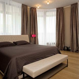 Esempio di una camera degli ospiti design di medie dimensioni con pareti beige, pavimento in legno massello medio, nessun camino e pavimento giallo