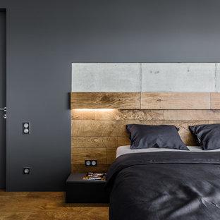 На фото: хозяйская спальня в современном стиле с черными стенами и коричневым полом