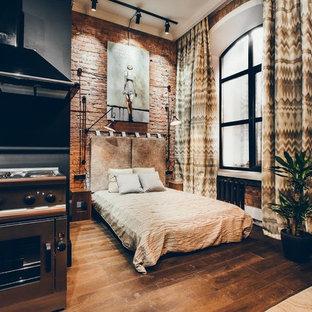 Modelo de dormitorio industrial con paredes rojas, suelo de madera oscura y suelo marrón