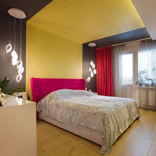 Foto de dormitorio principal, contemporáneo, de tamaño medio, sin chimenea, con paredes amarillas, suelo de madera clara y suelo amarillo