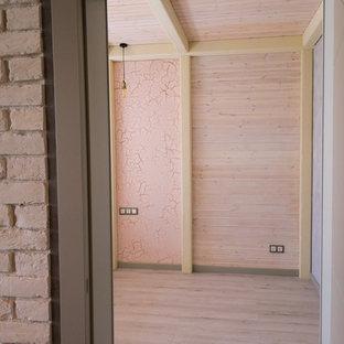 Стильный дизайн: хозяйская спальня среднего размера в стиле лофт с серыми стенами, полом из ламината, горизонтальным камином, фасадом камина из штукатурки и серым полом - последний тренд