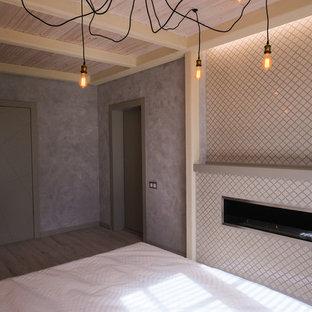 Идея дизайна: хозяйская спальня среднего размера в стиле лофт с серыми стенами, полом из ламината, горизонтальным камином, фасадом камина из штукатурки и серым полом
