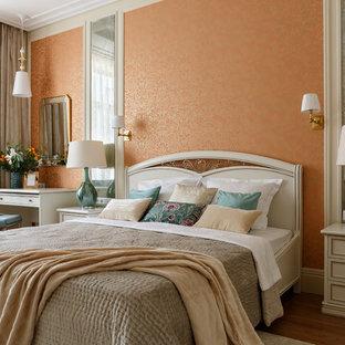 Modelo de dormitorio principal, clásico renovado, con parades naranjas, suelo de madera oscura y suelo marrón