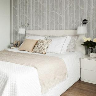 Пример оригинального дизайна: гостевая спальня в современном стиле с серыми стенами и паркетным полом среднего тона