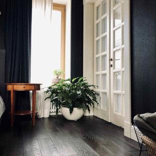 Ejemplo de dormitorio principal, clásico renovado, grande, con paredes negras, suelo de madera oscura, chimenea de esquina, marco de chimenea de metal y suelo negro