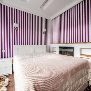 Ejemplo de habitación de invitados bandeja y madera, actual, grande, con paredes rosas, suelo laminado, chimenea lineal, marco de chimenea de madera, suelo marrón y madera