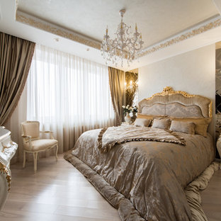 Inspiration pour une chambre parentale traditionnelle de taille moyenne avec un mur beige, un sol en bois clair et aucune cheminée.