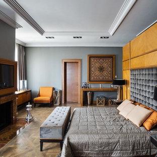 Неиссякаемый источник вдохновения для домашнего уюта: спальня в стиле современная классика с серыми стенами, паркетным полом среднего тона, стандартным камином, фасадом камина из камня и коричневым полом