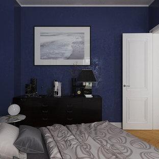 Diseño de dormitorio principal, urbano, de tamaño medio, con paredes azules y suelo de madera clara