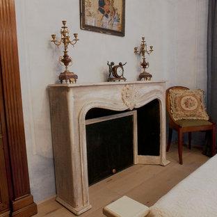 Imagen de dormitorio principal, vintage, de tamaño medio, con suelo de madera en tonos medios, chimenea lineal, marco de chimenea de madera y suelo beige