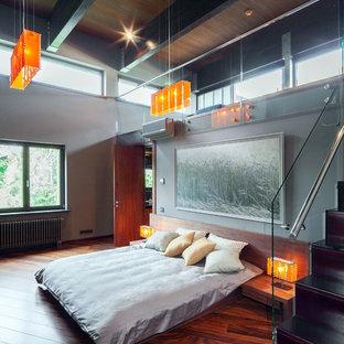 На фото: спальни на антресоли в современном стиле с серыми стенами и паркетным полом среднего тона без камина