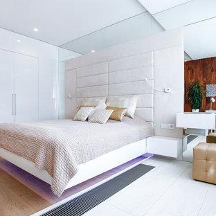 На фото: спальня в современном стиле с белыми стенами, паркетным полом среднего тона и коричневым полом с