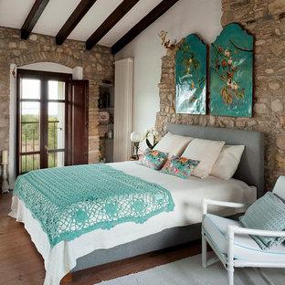 Immagine di una camera da letto country con pareti bianche, parquet scuro e pavimento marrone